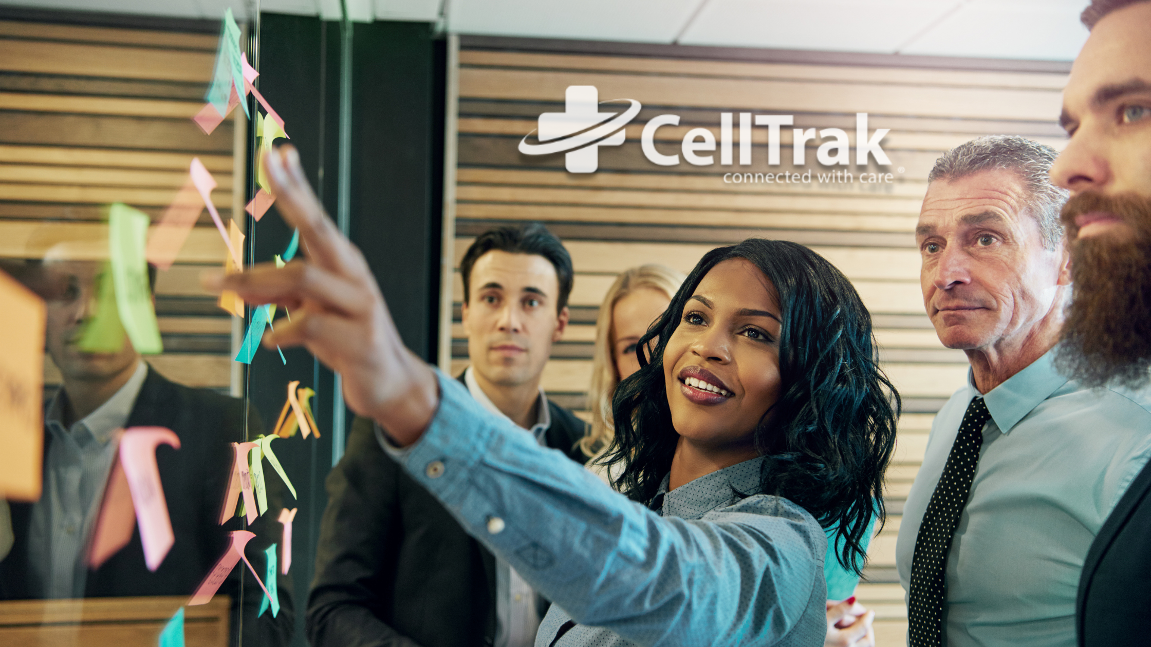 people working together in a meeting with celltrak logo in the background
